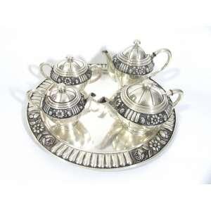 Jogo de chá em prata de lei portuguesa contrastada Mergulhão, teor 833, composto por bandeja, cafeteira, cremeira, chaleira e açucareiro. Med. A: 17 L: 23 P: 13 cm. (maior peça); med D: 44 cm. (bandeja)
