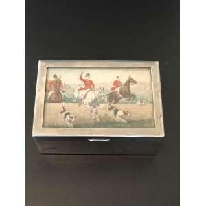 Linda caixa de metal com motivo de caçada, revestida de madeira. Medida de 14cm x 9cm x 6cm. <br /><br /><br><br>Beautiful metal box with hunting motif, covered with wood. Measure of 14cm x 9cm x 6cm.