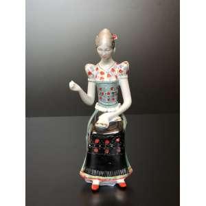 Estátua européia representando moça tecelã.<br />Medida de 23cm de altura.<br /><br />European statue of weaving girl.<br />Measure of 23cm in height.