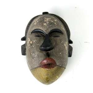 Máscara africana de madeira entalhada, patinada em tons de cinza, amarelo, preto e vermelho. Alt. 30 x 20 x 20cm. África, início séc. XX