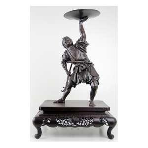 Escultura de bronze patinado representando figura de guerreiro mitológico, sobre base de madeira entalhada e fenestrada. Alt. 55 x 35 x 28cm. Japão, séc. XIX (base com pequeno trincado)