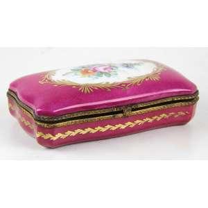 Caixa de porcelana na tonalidade rosa, decorada com douração e motivos florais em reservas, marca da manufatura Limoges sob a base. Alt. 04 x 15 x 08cm. França, séc. XX