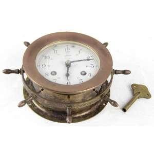 Relógio de mesa em forma de timão, marca da manufatura Schatz - modelo Ships Bell, máquina à corda (com chave). Alt. 06 x 17cm. Alemanha, séc. XX (não testado / pode precisar revisão)