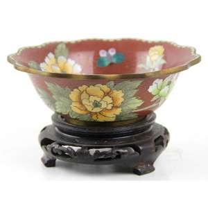 Bowl de metal com esmalte cloisonné, decorado com motivos florais sobre fundo na tonalidade vermelha, sobre base de madeira. Alt. 09 x 16cm (total). China, séc. XX