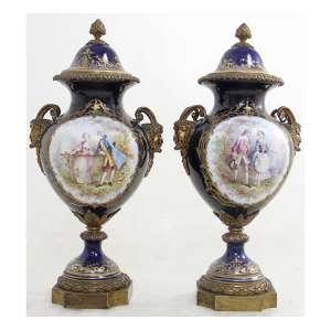Par de ânforas de porcelana, decoradas com cenas idílicas esmaltadas,assinados G.PORTEIVI, fundo na tonalidade azul cobalto, contém douração e alças laterais em forma de faunos, marca da manufatura Sèvres sob as tampas. Alt. 53x25x21cm. França,XIX.