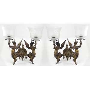 Par de arandelas de parede, estrutura de bronze com resquício de patina, ricamente decorado com figuras mitológicas segurando tochas, acompanha par de cúpulas de vidro acidadas. Alt. 44 x 36 x 34cm. (total cada). Europa, séc. XIX