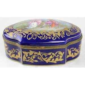 Caixa de porcelana na tonalidade azul cobalto, decorada com douração e cena idílica assinada A. GILBERT em reserva central da tampa, marca da manufatura Sèvres - B sob a base. Alt. 09 x 19 x 11cm. França, início séc. XX