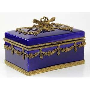 Caixa de porcelana esmaltada na tonalidade azul cobalto com detalhes de bronze patinado, marca da manufatura MP-Sèvres sob a base. Alt. 13 x 18 x 12cm. França, séc. XX (caixa no estado / com restauro e pequeno bicado)