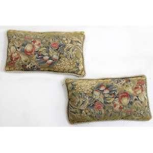 Par de almofadas com forração petit-point representando frutos, laterais trançadas. 56 x 33cm cada. Europa,séc. XIX