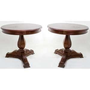 Par de mesas auxiliares, estrutura de madeira de rádica, fuste facetado, pés entalhados ligeiramente recurvos e tampo circular. Alt. 72 x 85cm cada. Europa, séc. XX.