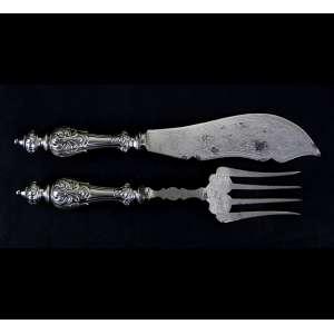 Par de talheres para servir peixe, estrutura de prata-de-lei sem contraste com fino trabalho de cinzel. Comp. 26x05 e 24x05cm. Europa, início séc. XX