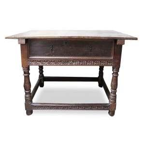 Mesa com estrutura de madeira patinada, pernas torneadas, detalhes frontais entalhados, contém uma gaveta com dois puxadores de ferro originais de época. Alt. 90 x 128 x 84cm. Séc. XIX