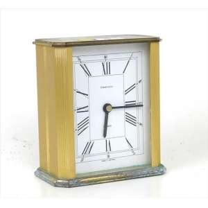 TIFFANY & Co., Relógio de mesa a quartzo, caixa de metal dourado, mostrador com algarismos romanos. Alt. 12x11x06cm.. (precisa revisão e restauro na base )