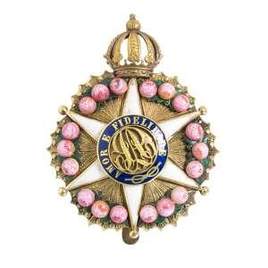 """<b>Imperial Ordem da Rosa - Insígnia de Comendador - séc. XIX</b><br><br>ouro e esmaltes. Anverso com estrela em esmalte branco de seis pontas maçanetadas, bordada por guirlanda de rosas, deitada sobre resplendor, tendo ao centro medalhão cercado por orla azul realçada pelas palavras """"AMOR E FIDELIDADE"""" contornando iniciais """"P"""" e """"A"""" entrelaçadas, encimada por coroa imperial. Reverso com acabamento liso apresentando a inscrição """"Offerta do Corpo de Bombeiros ao Major Miguel Maria Girard, em signal de subido apreço aos seus distintos serviços – Agosto – 1882"""" (centro desalinhado e uma rosa solta)<br><br>6 x 4,5 cm - 26 g"""