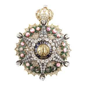 """<b>Imperial Ordem da Rosa - Insígnia de Grande Dignitário - séc. XIX</b><br><br>ouro, esmaltes e diamantes. Anverso com estrela de seis pontas maçanetadas e cravadas com diamantes, deitada sobre guirlanda de rosas e resplendor, tendo ao centro medalhão cercado por orla azul realçada pelas palavras """"AMOR E FIDELIDADE"""" contornando iniciais """"P"""" e """"A"""" entrelaçadas, topo com coroa imperial ornamentada por diamantes. Reverso em ouro lavrado e gravado com estilizações e rosas, fecho vertical com pino (faltam dois diamantes na coroa e seis rosas)<br><br>8,5 x 6 cm - 67 g"""