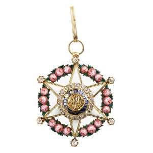 """<b>Imperial Ordem da Rosa - Insígnia provavelmente de Dignitário ou de Comendador - séc. XIX</b><br><br>ouro, esmaltes e diamantes. Anverso com estrela em esmalte branco de seis pontas maçanetadas e rematadas por brilhantes, deitada sobre guirlanda de rosas, tendo ao centro medalhão com diamantes cravados e orla azul realçada pelas palavras """"AMOR E FIDELIDADE"""" contornando iniciais """"P"""" e """"A"""" entrelaçadas, encimado por argola e contra-argola de sustentação. Reverso igual ao anverso, porém sem medalhão central (desgastes no esmalte)<br><br>6,2 x 5 cm - 30 g"""