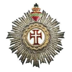 """<b>Ordem de Nosso Senhor Jesus Cristo - Insígnia de Dignitário ou de Comendador - séc. XIX</b><br><br>prata, ouro e esmaltes. No anverso, grande resplendor circundando medalhão circular de cor branca, ornado com bordas peroladas centralizando cruz da Ordem de Cristo bordada em vermelho, filetada em dourado e centralizando pequena cruz latina branca, ornamentada no topo por Sagrado Coração atravessado por coroa de espinhos em esmalte verde e pequena cruz de cor azul. Reverso com acabamento em metal liso apresentando inscrição gravada e desgastada """"Caetano Pinheiro da Fonseca os seus amigos 16 de Novr de 1870"""" e fecho vertical com alfinete<br><br>6 x 5,5 cm - 29 g"""