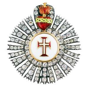 """<b>Ordem de Nosso Senhor Jesus Cristo - Insígnia de Dignitário ou de Comendador - séc. XIX</b><br><br>prata, ouro, esmaltes e pedras possivelmente diamantes, crisólitas ou """"minas novas"""" (quartzos e topázios). No anverso, grande resplendor cravejado com pedras alinhadas, tendo ao centro medalhão circular branco com cercadura adiamantada e anelado em ouro, apresentando cruz da Ordem de Cristo bordada em vermelho, filetada em dourado, centralizando pequena cruz latina branca, rematada no topo por anel de sustentação ornamentada à frente por Coração Flamejante atravessado por coroa de espinhos em esmalte verde e encimado por pequena cruz. Reverso com acabamento em metal liso e fecho vertical com alfinete duplo<br><br>6 x 5,5 cm - 45 g"""