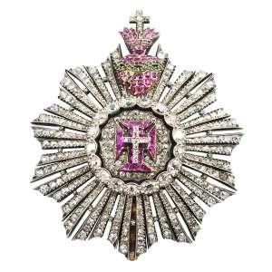 """<b>Ordem de Nosso Senhor Jesus Cristo - Insígnia de Grã-Cruz ou de Dignitário - séc. XIX</b><br><br>ouro, prata vermeil, prata, diamantes, rubis e esmeraldas. No anverso, grande resplendor inteiramente cravejado com diamantes, formada por feixes com quatro raios e dispostos em leque à volta de borda anelada, ostentando no centro medalhão em """"pavê"""" adiamantado e cruz da Ordem de Cristo ornamentada por rubis e sustentando pequena cruz latina, exibindo no topo Sagrado Coração flamejante com rubis, atravessado por fitas entrelaçadas em esmeraldas e encimado por pequena cruz. Reverso com acabamento em metal liso gravado com as iniciais A.C.P. e fecho vertical com clip lavrado com volutas (falta uma esmeralda)<br><br>7,5 x 6 cm - 56 g"""