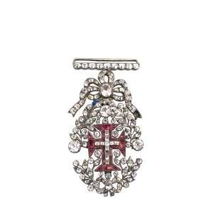 """<b>Ordem de Nosso Senhor Jesus Cristo - Insígnia de Cavaleiro - final do séc. XVIII</b><br><br>prata vermeil, granadas e outras pedras, provavelmente diamantes ou parecendo diamantes como crisólitas ou """"minas novas"""" (quartzos e topázios). No anverso, cruz da Ordem de Cristo cravejada com granadas vermelhas tendo ao centro pequena cruz latina adiamantada e deitada sobre adorno ovalado formando palmas realçadas por diamantes lapidados em rose cut, parte superior com laço e passador de fita ornados por pedras. Reverso com acabamento em metal liso<br><br>6 x 3,3 cm - 21 g"""