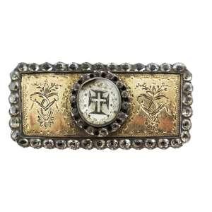 """<b>Ordem de Nosso Senhor Jesus Cristo - Barreta - séc. XIX</b><br><br>prata vermeil, ouro, esmaltes e pedras possivelmente diamantes, crisólitas ou """"minas novas"""" (quartzos e topázios). No anverso, placa retangular com borda adiamantada e composições florais cinzeladas, centralizando medalhão oval branco com pequena cruz latina deitada sobre cruz da Ordem de Cristo. Reverso com acabamento em metal liso e fecho horizontal com alfinete (marcas de uso)<br><br>1,5 x 3,5 cm - 13 g"""