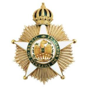 """<b>Imperial Ordem de Dom Pedro I - Insígnia provavelmente de Grã-Cruz - séc. XIX</b><br><br>ouro e esmaltes. No anverso, estrela em esmalte branco de cinco pontas maçanetadas, deitada em resplendor, tendo ao centro medalhão de fundo branco com dragão de asas abertas e escudo no peito com as iniciais """"P.I."""" sobre coroa de sete pontas, circundado por orla em esmalte verde-bandeira com a legenda """"FUNDADOR DO IMPÉRIO DO BRAZIL"""", encimado por coroa imperial. Reverso lavrado com guilhochê e fecho vertical com alfinete<br><br>8,5 x 6,5 cm - 81 g"""