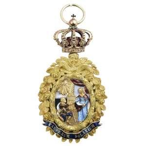 """<b>Ordem Real de Santa Isabel - Insígnia de Dama - 1801</b><br><br>ouro e esmaltes. Anverso com medalhão oval bordado por guirlanda de rosas cinzeladas, tendo ao centro cena em esmaltes policromados, realçada na parte inferior por fita com a legenda """"PAUPERUM SOLATIUM"""" (conforto dos pobres), topo com coroa do Reino de Portugal. Reverso com idêntica guirlanda de rosas cinzeladas, porém apresentando alteração no medalhão substituindo-o pelas iniciais """"I' e """"C"""" entrelaçadas e data de """"MDCCCI"""" sobre fundo em esmalte branco e cercadas por orla azul com a legenda """"REAL ORDEM DE SANTA ISABEL""""<br><br>9,5 x 4,5 cm - 78g"""