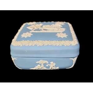Linda caixinha de biscuit inglês Wedgwood, com 5 ornamentos diferenciados todos no estilo romano, aplicados no tampo e nos 4 lados da caixa. 11cm de lado x 5cm altura. O tampo contém 4 partes brancas restauradas conforme fotos.