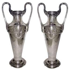 Par de belos vasos alemães monogramadas, marca da manufatura WMF, em metal espessurado a prata, decoradas com guirlandas, medalhões, flores e volutas em relevo. (pequena perda no prateado e um com pequena mossa). Alt. 57 cm