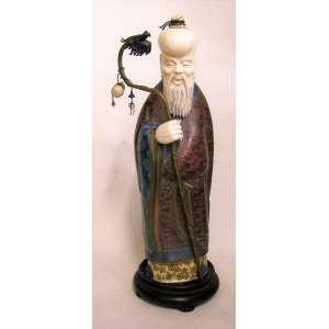 Antiga e rara escultura em marfim e cloisoné policromado, representando Andarilho. Cajado em metal e cabeça de dragão em cloisoné. Base em madeira. Alt. da escultura 31 cm.