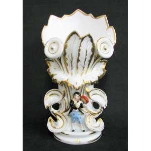 Belo vaso em porcelana francesa, Velho Paris, policromado com trabalhos em relevo de folhagens e figura de jovem tocando pandeiro. Detalhes em dourado. Alt. 36 cm.