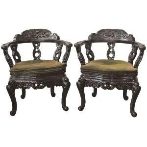Belo par de cadeiras de braços orientais, em madeira nobre ricamente entalhada, tendo no encosto dragões alados. Pernas recurvas. (falta pequeno pino de acabamento em 1 braço e encosto necessita restauro). Med. 87x66x48,5cm.
