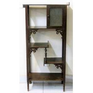Porta bibelô, estilo Art-Noveau, em madeira entalhada, com 5 prateleiras e pequeno escaninho com 1 porta com vidro. (falta parte do adereço). Med. 123x60x26cm.
