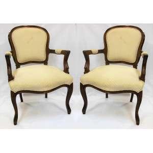 Par de cadeiras de braço estilo Luís XV, em madeira entalhada. Estofadas e forradas com tecido no tom creme. Pernas recurvas. Med. 98x66x62 cm.