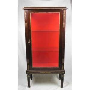 Vitrine estilo Inglês em madeira nobre com apliques em metal cinzelado. Porta, tampo e laterais em vidro. Interior com 2 prateleiras e fundo forrado em veludo vermelho. Med. 133x65x32cm.