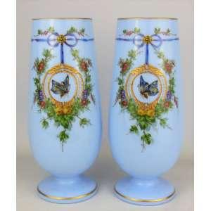 Belíssimo e elegante par de vasos em opalina européia, do Séc. XIX, possivelmente Baccarat, no tom azul, decorados com pinturas em policromia e toques esmaltados, de flores, folhagens e laço, tendo em reserva borboleta. Detalhes em dourado. Alt. 30cm.