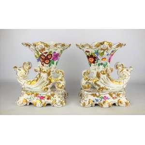 Par de belas e elegantes floreiras, na forma de cornucópias, em porcelana européia, possivelmente francesa, ricamente decorada ao gosto Vieux Paris, com pinturas florais e detalhes em dourado. Marca da manufatura nas bases. Med. 23x20x14,5cm.