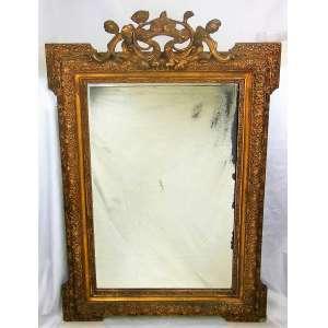 Belo espelho bisotado com moldura em madeira dourada e entalhada, decorada com delicados trabalhos de flores, folhas e arabescos. Florão no ápice. Espelho com manchas do tempo e moldura com pequenas perdas no dourado. Med. 117x84 cm.