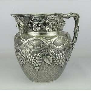 Bela jarra em prata cinzelada em parreiras, cachos de uva e perolados. Bico na forma de rosto de baco. Apresenta resquício de contraste na base, sendo possivelmente portuguesa. Med. 19,5x23,5x17,5cm. Peso 1.010g.