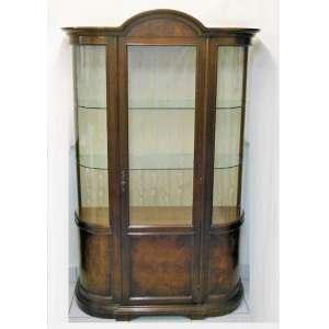 Bela vitrine em madeira entalhada, laterais bombé e porta central com vidros. Interior com 4 prateleiras, sendo duas inferiores em madeiras e duas superiores em vidro. Fundo forrado em tecido. Med. 1,95x1,19x40cm.