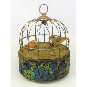 Raro porta joias de coleção com caixa de musica, na forma de gaiola em metal com dois pássaros, sendo que um está sobre um balanço que se move quando uma gaveta é aberta. Parte inferior da gaiola forrada em tecido. Funcionando. Med. 22x16,5cm.
