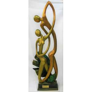Benigno - Grande grupo escultórico em madeira patinada no tom dourado e cobreado, representando Harmonia. Adornado com grande folha em metal. Assinada e dat. 1985. Alt. total 185cm.