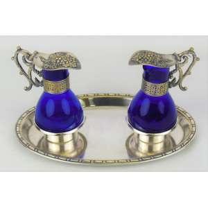 Galheteiro em metal espessurado a prata com 2 recipientes em vidro azul cobalto. Med. 12x23x13,5cm.