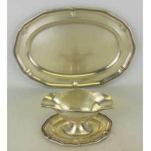 Travessa e molheira em prata espanhola, teor 916 milésimos, com marca de contraste e do prateiro, bordas recortadas trabalhadas em frisos. Comp. travessa 43cm. Peso: 1.460g.