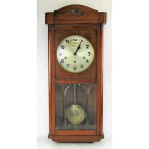 Relógio de parede carrilhão com caixa em madeira entalhada. Porta com vidro bisotado na parte inferior. Mostrador em metal. Com chave e pendulo. Maquina necessita reparo. Med. 74,5x32x19cm.