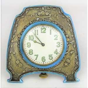 Belo, raro e antigo relógio europeu de coleção e viagem na forma de relógio de bolso. Caixa em prata trabalhada com flores, folhas e floreira, com pintura esmaltada na cor azul. Funcionando. Med. 10x9,5 cm.
