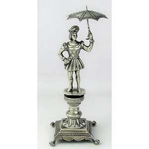 Paliteiro de coleção, em prata portuguesa, contraste L coroado, prateiro FJT, na forma de serviçal com sombrinha, sobre pedestal. Base com pés em pata. Alt. 18cm.
