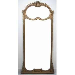 Belo e grande espelho bisotado, de chão ou parede, com moldura dourada e entalhada com vaso de flores, volutas e folhagens. Moldura com discretíssima perda em uma pontinha. Espelhos superior e central recortados e com bisotados. Acompanha base/peanha, de pendurar, em madeira. Med.207x97cm (sem base) e 215,5x98cm (com a base).