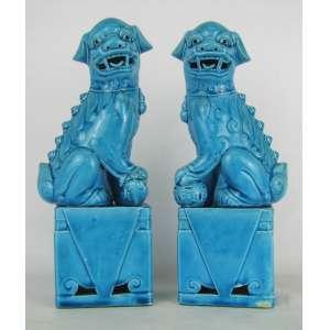 Par de estatuetas em porcelana no tom azul representando Cães fó. Alts. 24,5cm.