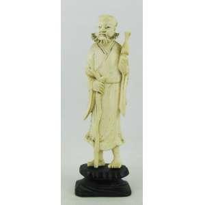 Escultura em marfim monobloco, representando Andarilho com cajado. Base em madeira. China, período Revolucionário. Alt. total 15cm.